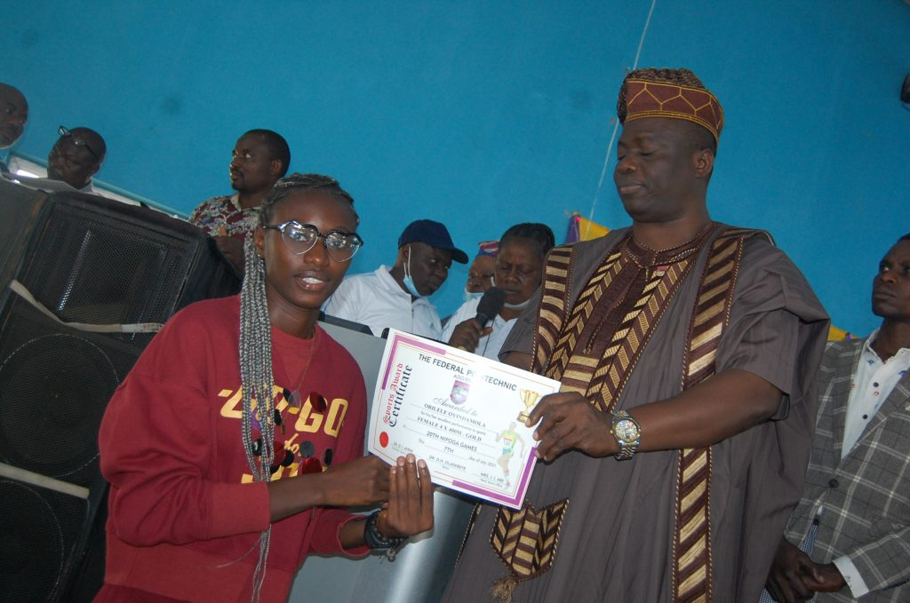 One of the athlete receiving a certificate of merit from the Rector Dr. Dayo Oladebeye.